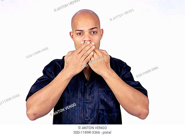 Young man with his hands on his mouth