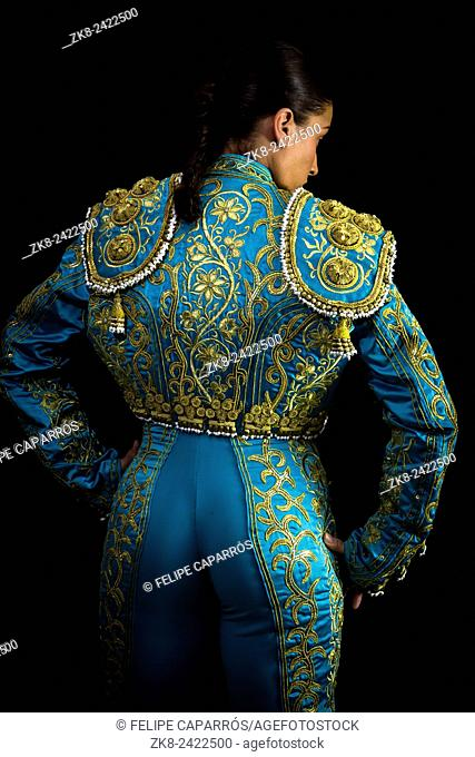 Woman bullfighter suit with blue lights on a black background