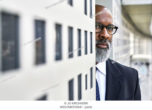 Mature businessman standing by wall, looking worried