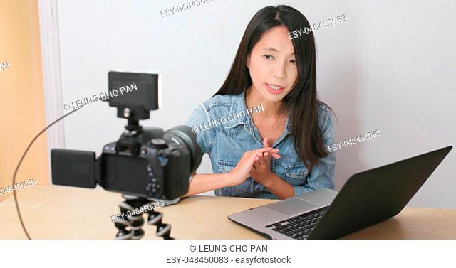 Woman taking video and present with notebook computer at home