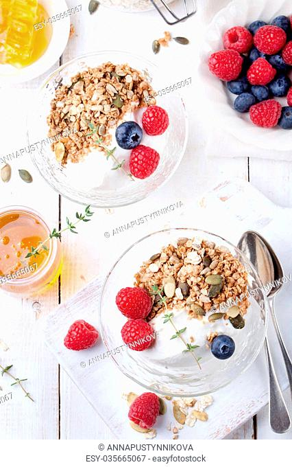 Healthy breakfast. Granola with pumpkin seeds, honey, yogurt and fresh berries in a ceramic bowl on white background