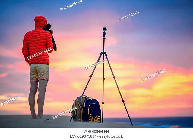 Photographer in red jacket with hood filming with small action camera on the tripod beautiful sunrise on the sand dunes in the early morning