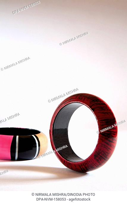 Colourful wooden bangles on white background