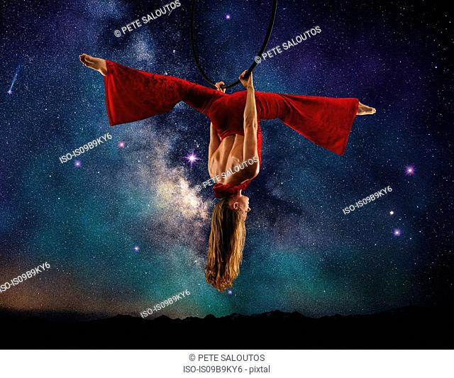 Young female aerial acrobat doing splits hanging upside down from hoop, milky way background