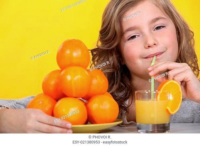 Little girl drinking freshly squeezed orange juice