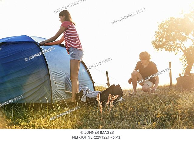 Young couple putting tent up