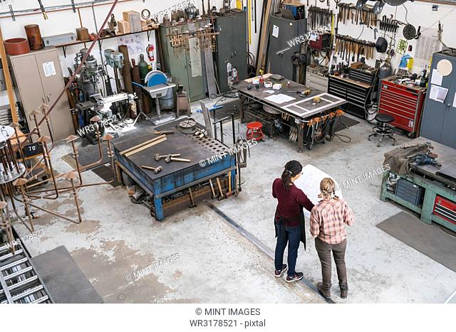 High angle view of two women standing in metal workshop, holding technical blueprint