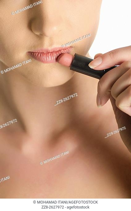 Close up of a young woman applying lipstick
