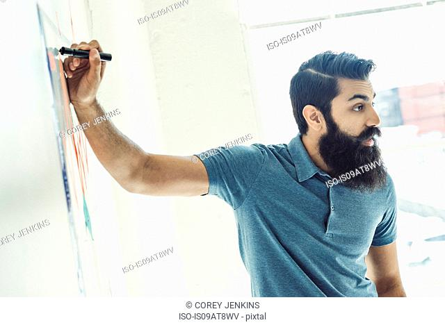 Businessman writing on wall chart in office