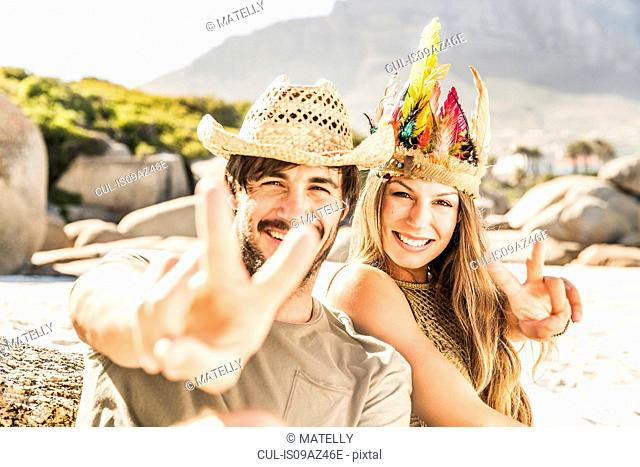 Portrait of mid adult couple making peace sign on beach, Cape Town, South Africa