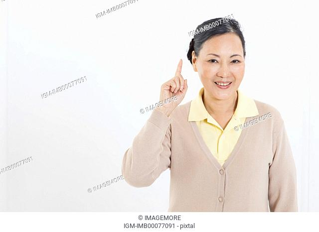 Senior woman smiling at the camera and pointing