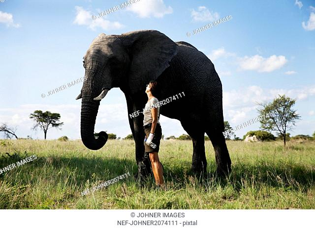 Mature woman standing next to elephant
