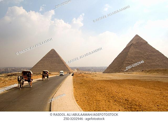 Cairo, Egypt – November 12, 2018: photo for Pyramid of Khufu in the Pyramids of Giza in Cairo city capital of Egypt. and Pyramid of Khafra and Horse-drawn carts