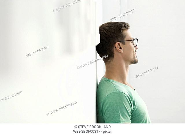 Young businessman in office leaning against wall