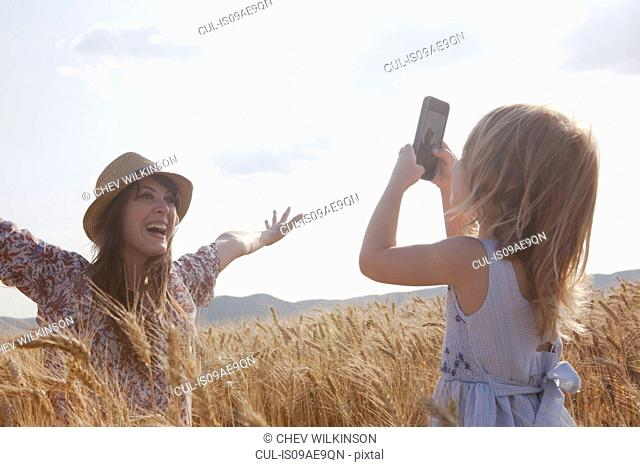 Girl taking photograph of mother in wheat field with arms open