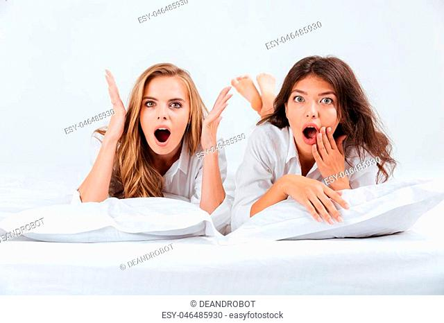Two pretty shocked women in shirts lying on white bed with pillows and looking at camera