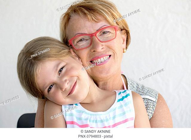Portrait of a little girl in the lap of her grandmother