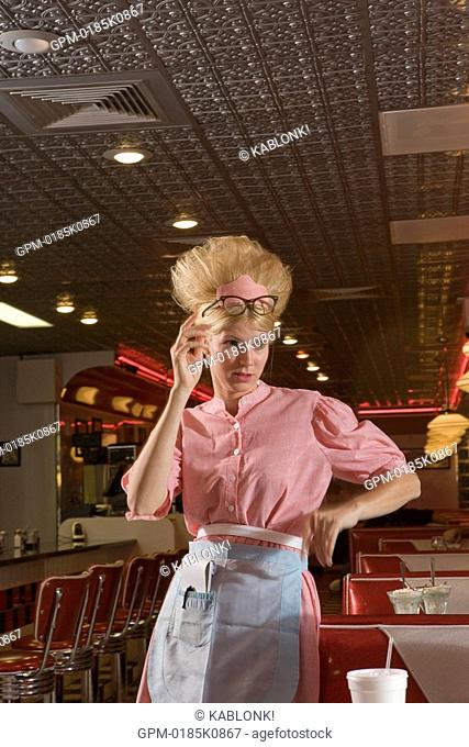 Young waitress in 1950s style uniform standing in old-fashioned diner