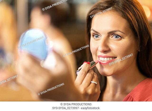 close up of woman with lipstick applying makeup