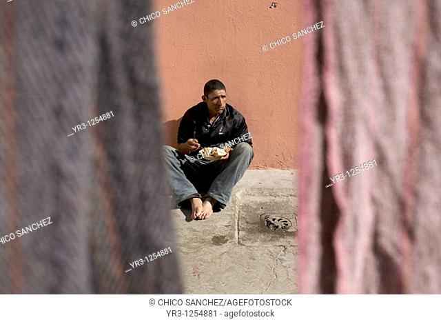 An undocumented Central American migrant traveling across Mexico to work in the United States eats as he sits on the patio floor of a shelter located along the...