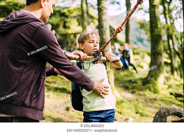 Courageous little boy has found a rope swing while hiking with his family. His father is helping him get on the rope swing