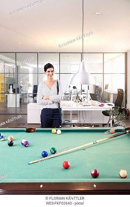 Businesswoman standing at pool table, playing billard, smiling