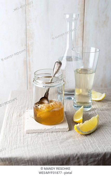 Honey jar with honeycomb and glass of water with honey