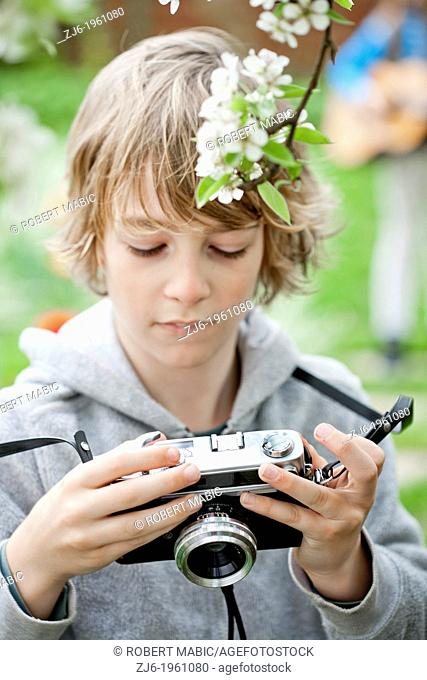 Boy playing with an old camera