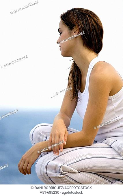 Young woman in white clothes looking at the sea