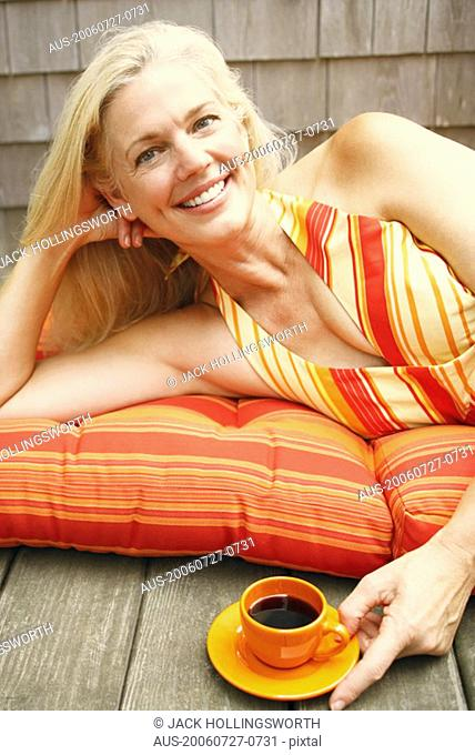 Portrait of a mature woman lying with a cup of black tea in front of her