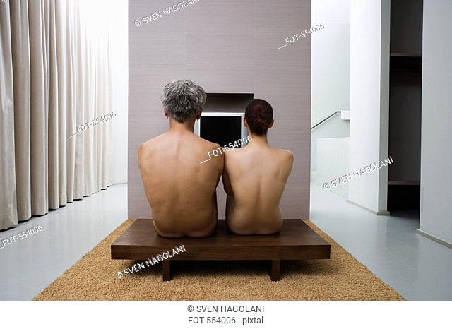 The backs of a naked man and woman sitting