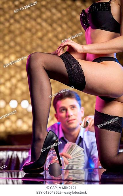 Close up of sexy striptease dancer taking off hose. Young man watching on background