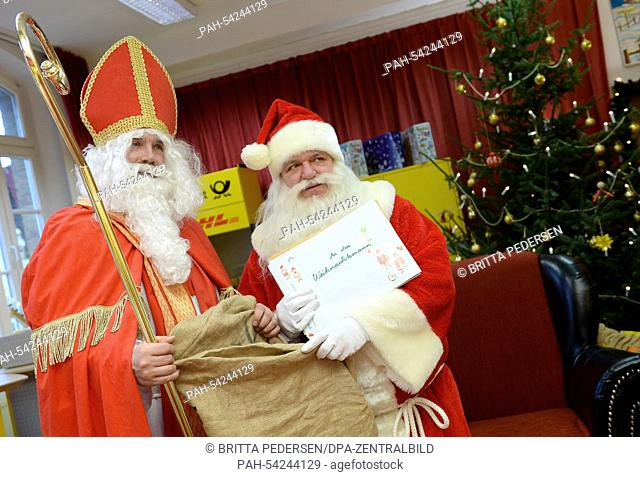 A man dressed as Sinterklaas (L), a Dutch version of Santa Claus, visits the Christmas post office in Himmelpfort, Germany, 10 December 2014