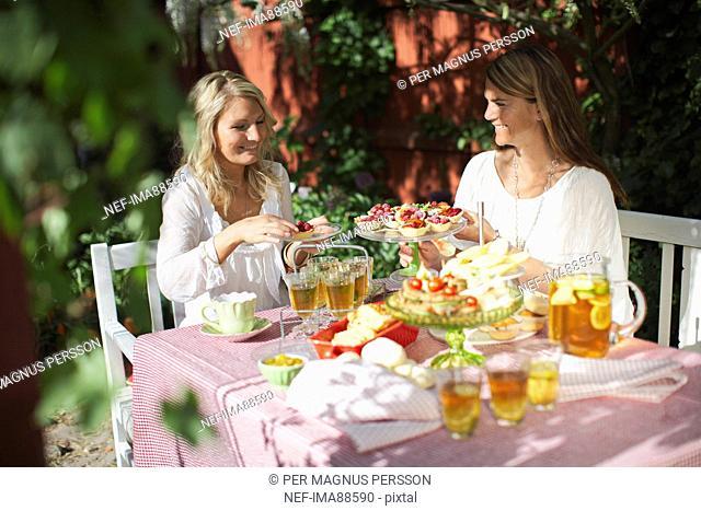 Two mid adult women having garden party