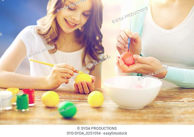 daughter and mother coloring easter eggs
