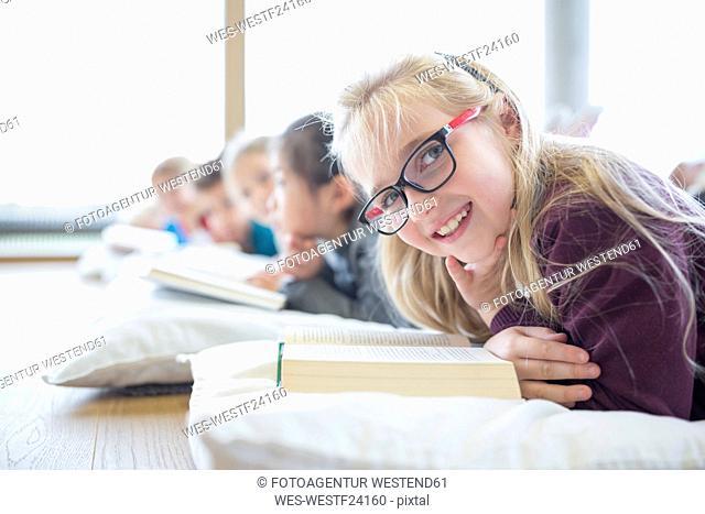 Portrait of smiling schoolgirl lying on the floor with classmates reading book in school break room