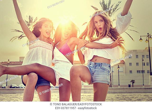 Best friends teen girls having fun on a beach sand at sunset