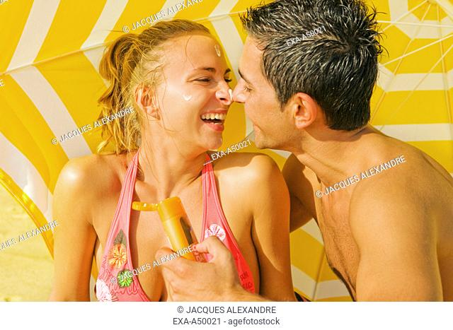 Ditsy young couple playing around with suncream on a beach