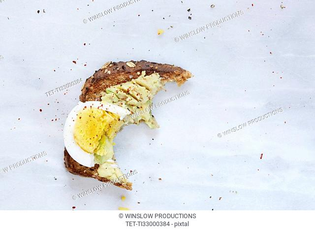 Missing bite of toasted bread with avocado and hard boiled egg