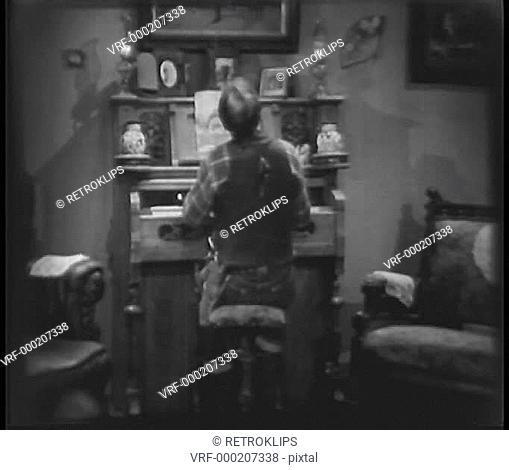 Rear view of man singing while playing a melodeon organ