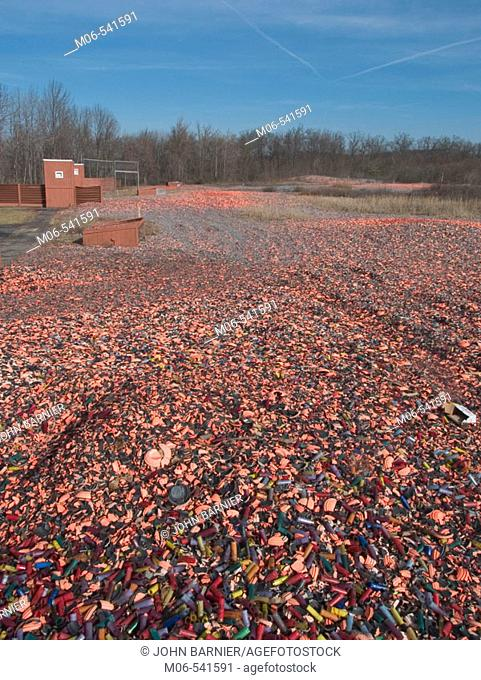 A blanket of spent shotgun shells covers a field in the United States. Mixed in with the shells are pieces of clay pigeons