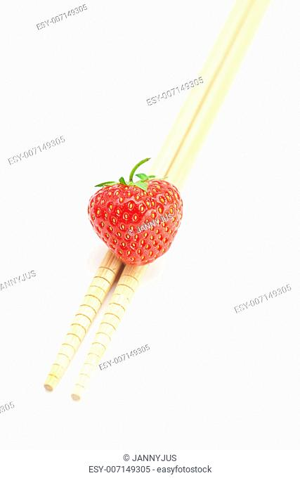 strawberry and chopsticks isolated on white