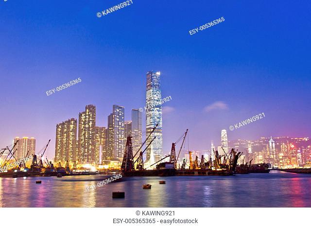Hong Kong harbor at sunset with industrial ships