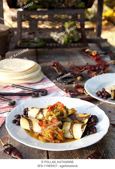 Black bean burritos and roasted chilli peppers on a wooden table outdoors