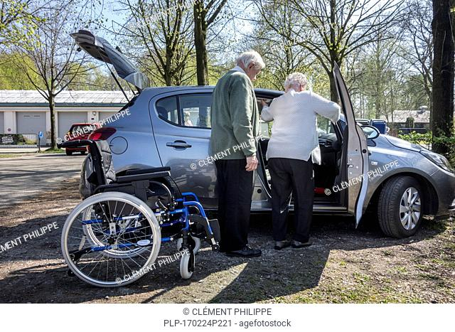 Retired husband helping physically disabled elderly wife from wheelchair entering car at parking