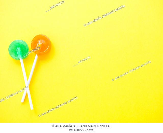 Green and orange lollipops on a yellow background
