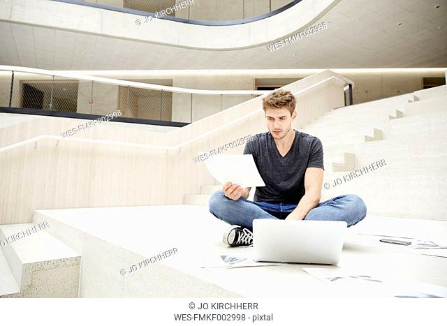Young man sitting on floor with laptop and papers