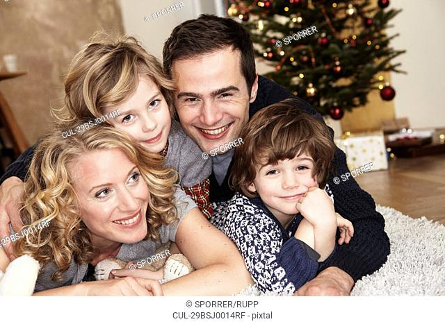 Family lying on carpet in front of tree