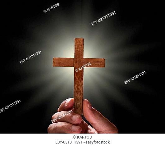 Hand with a cross against dark background, religious concept