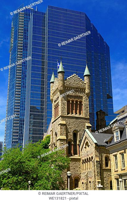 Old St Andrews presbyterian church tower against modern blue glass highrise office tower Toronto
